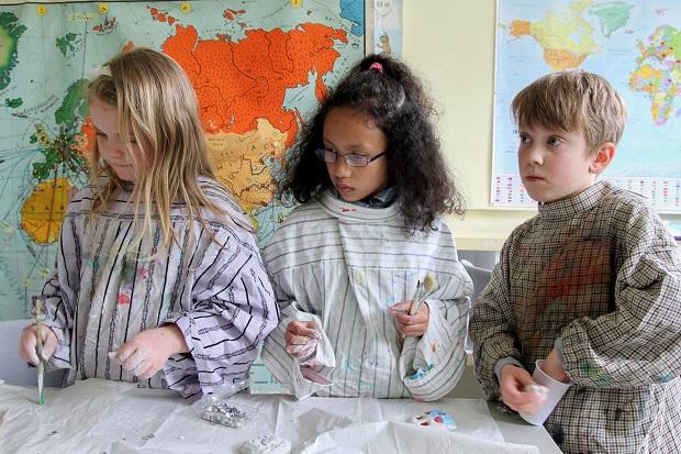 Schuelerinnen und Schueler der Grundschule gestalten Weltkarte mit 49 Nationen